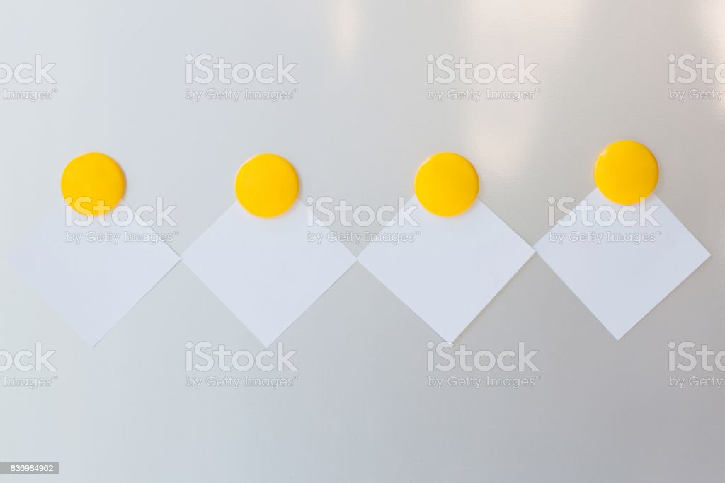 Yellow magnet put on on blank paper stock photo