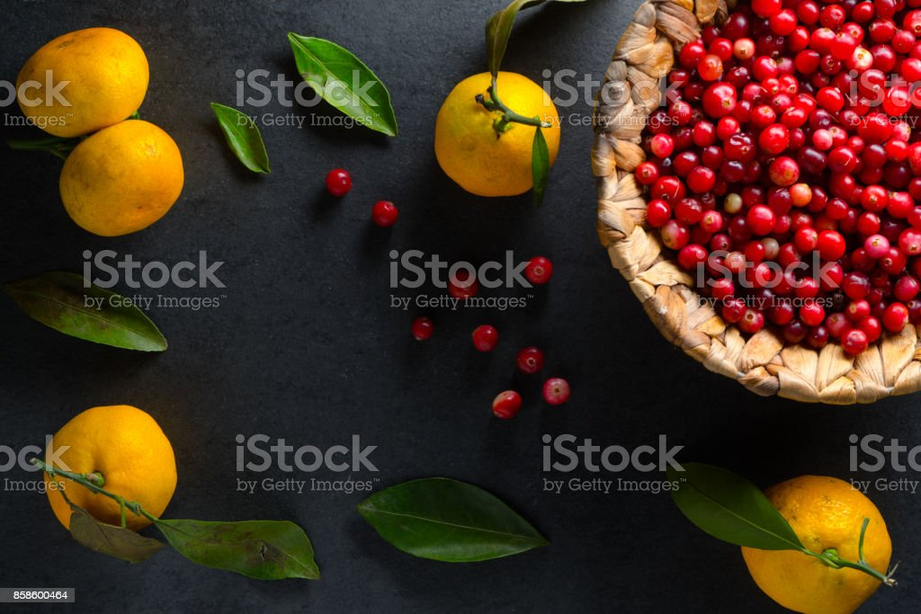 Yellow mandarins with leaves and cranberries in a basket on a gray stone free space stock photo