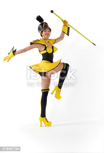 A beautiful young girl dressed in a yellow marching girls costume type uniform poses and salutes