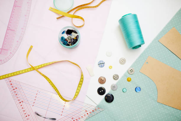 Yellow measuring tape, blue thread, colorful buttons, light blue cloth and cardboard pattern are lying in white table stock photo