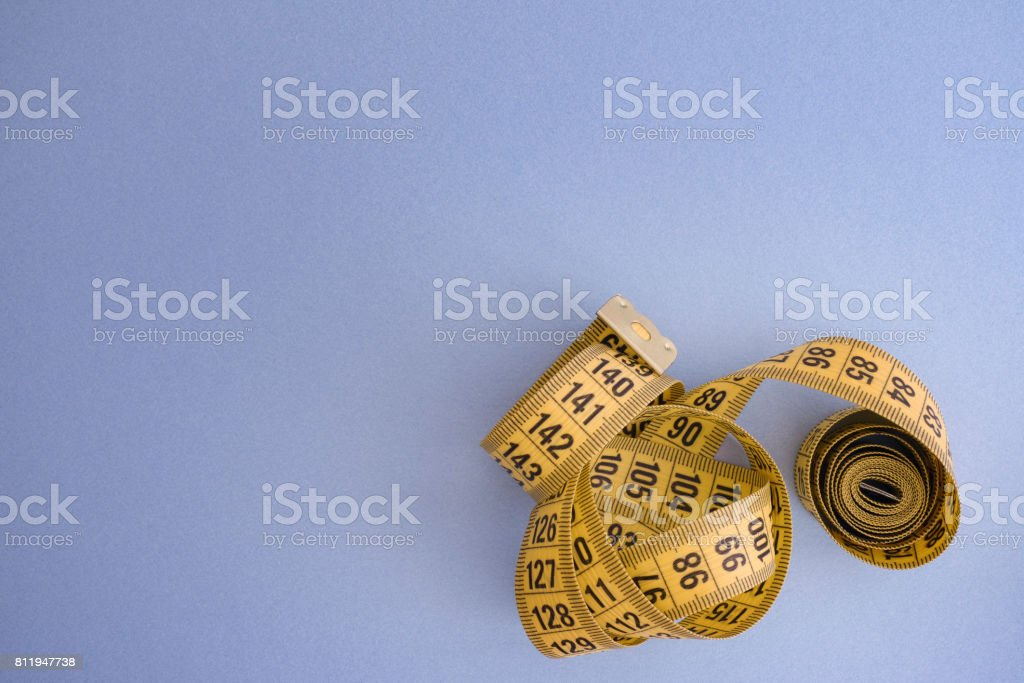 Yellow measuring tape on a blue background stock photo