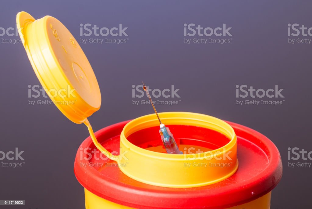 Yellow medical disposal waste box, syringe needle with red drop on the tip stock photo