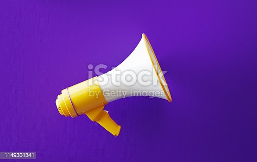 Yellow megaphone on purple background. Horizontal composition with copy space. Great use for announcement concepts.