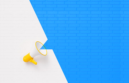 Yellow megaphone sitting over white and blue background. Horizontal composition with copy space. Announcement concept.