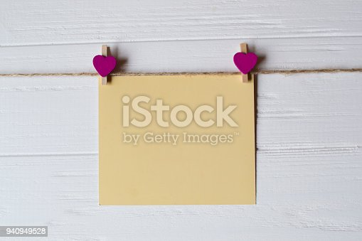 istock Yellow memo sheet fastened with a decorative pin on a white wooden board. 940949528