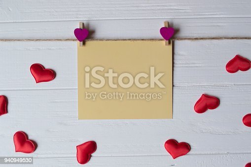 istock Yellow memo sheet fastened with a decorative pin on a white wooden board. 940949530