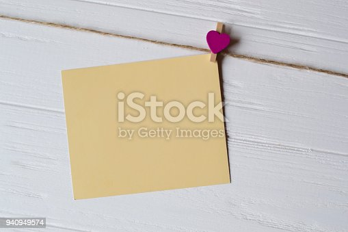 istock Yellow memo sheet fastened with a decorative pin on a white wooden board. 940949574