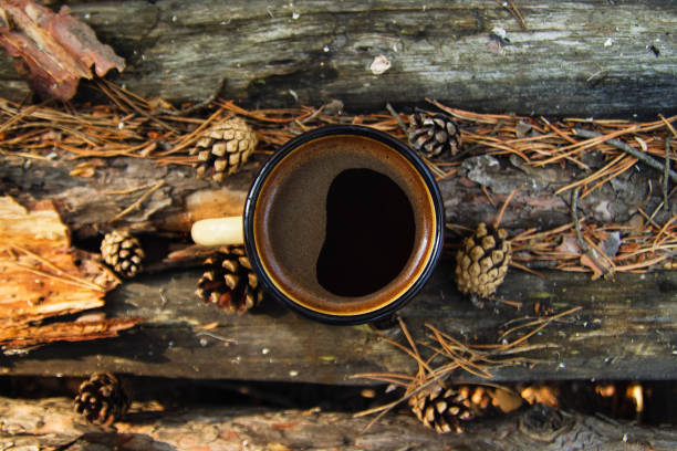 Yellow metal  cup with hot coffee on the wooden background with the coins, needles and bark of tree, top view. stock photo