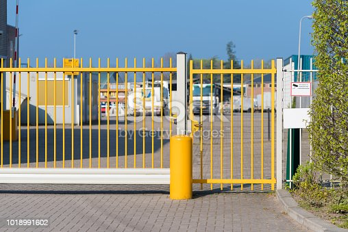 yellow automatic metal gate at an industrial area