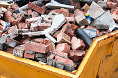 Yellow metal skip full of old bricks