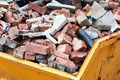 Yellow metal skip full of old bricks