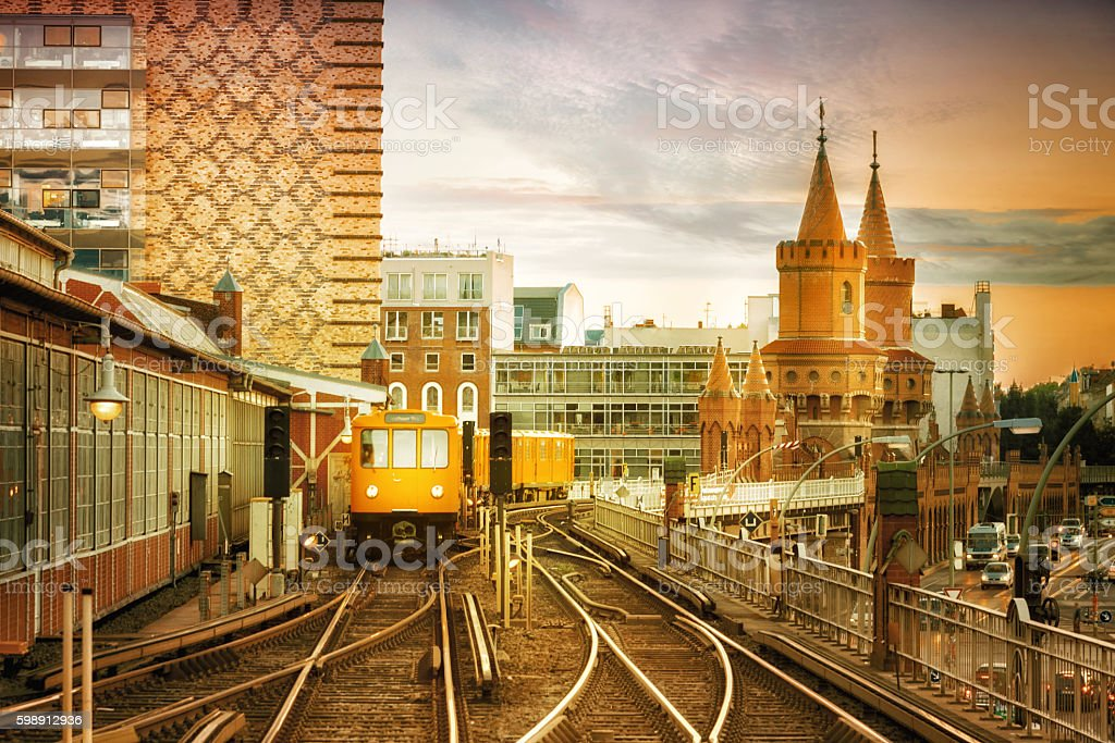 yellow metro train arriving at Station Oberbaumbrücke at sunset hour stock photo
