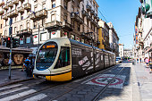 Milan, Italy - August 27, 2018: Yellow Milanese electric tram running through the heart of Milan city centre in Italy. The tramway network is an important part of the public transport network of Milan, Northern Italy.
