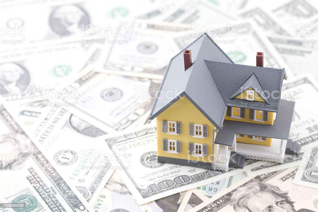 Yellow Miniature House on top of U.S. Money royalty-free stock photo
