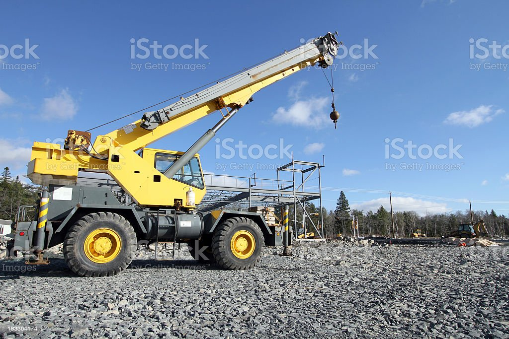 Yellow mobile construction crane driving over gray gravel stock photo