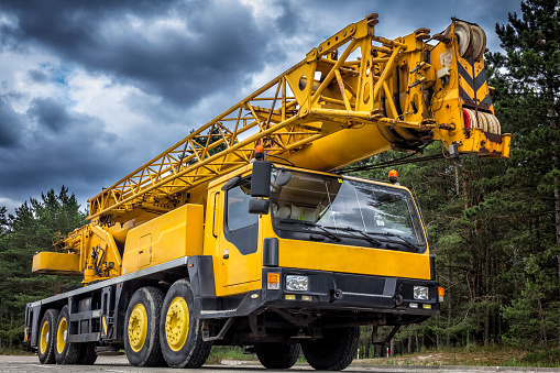 Yellow mobile crane in road construction