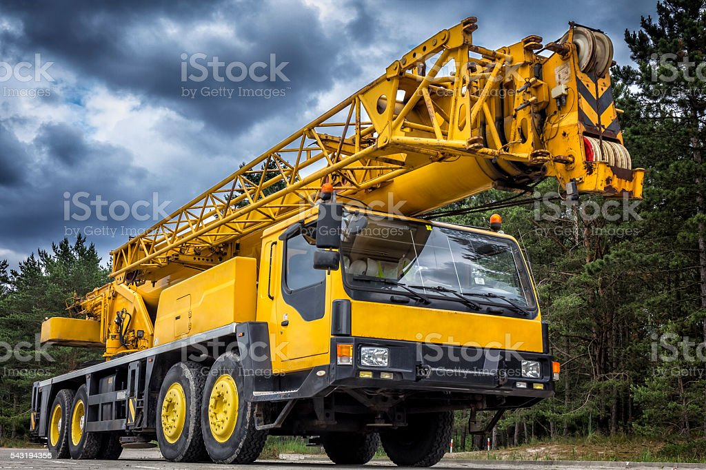 Yellow mobile crane in road construction stock photo
