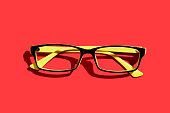 Yellow modern fashion glasses over head on red background, flat lay with sharp shadow