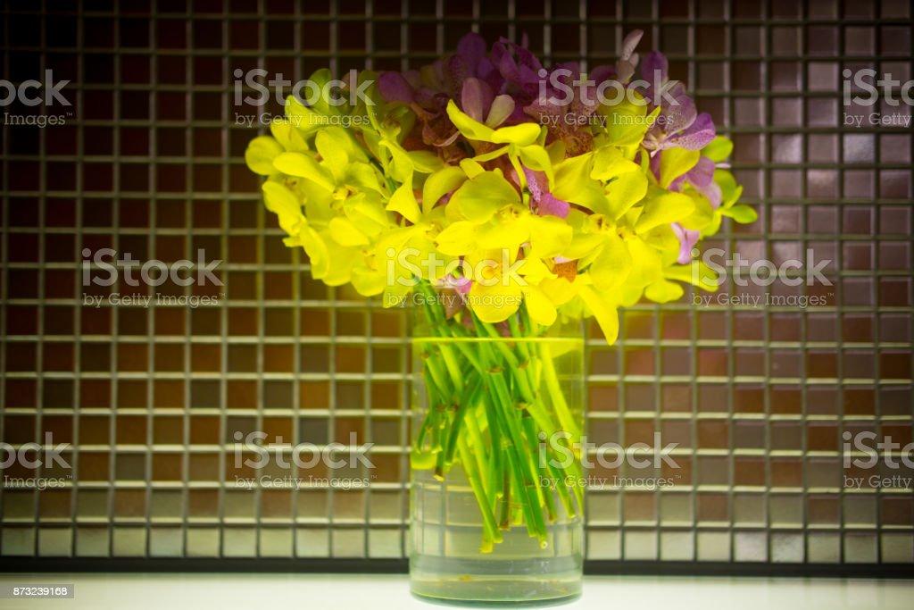 Yellow mokara orchid bouquet in glass pot stock photo