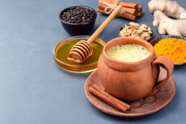 Yellow moon milk with turmeric in clay cup, ingredients on background, horizontal, copy space stock photo
