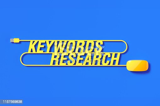 Yellow mouse cable forming keywords research text on blue background. Horizontal composition with copy space.