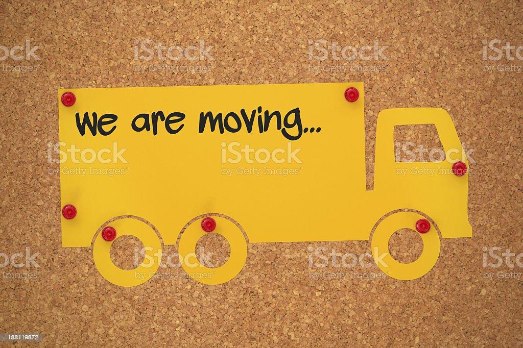 Yellow moving van cutout tacked to a cork board stock photo