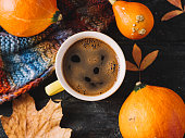 istock Yellow mug espresso coffee Cup on wooden table with autumn leaves, pumpkin and colorful autumn warm scarf . Warmth and comfort 1266986236