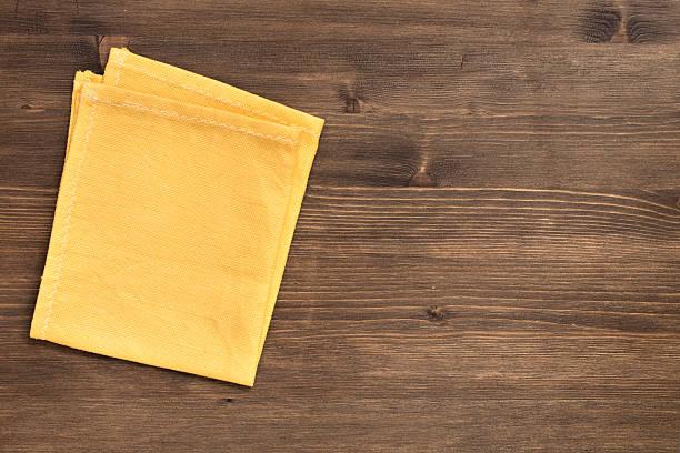 Cтоковое фото Желтый napkin на налево на деревянном фоне