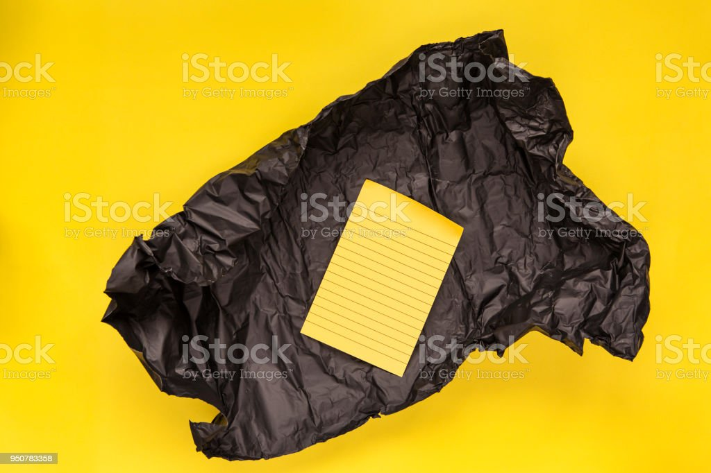 Yellow note paper in black wrapping paper on yellow background
