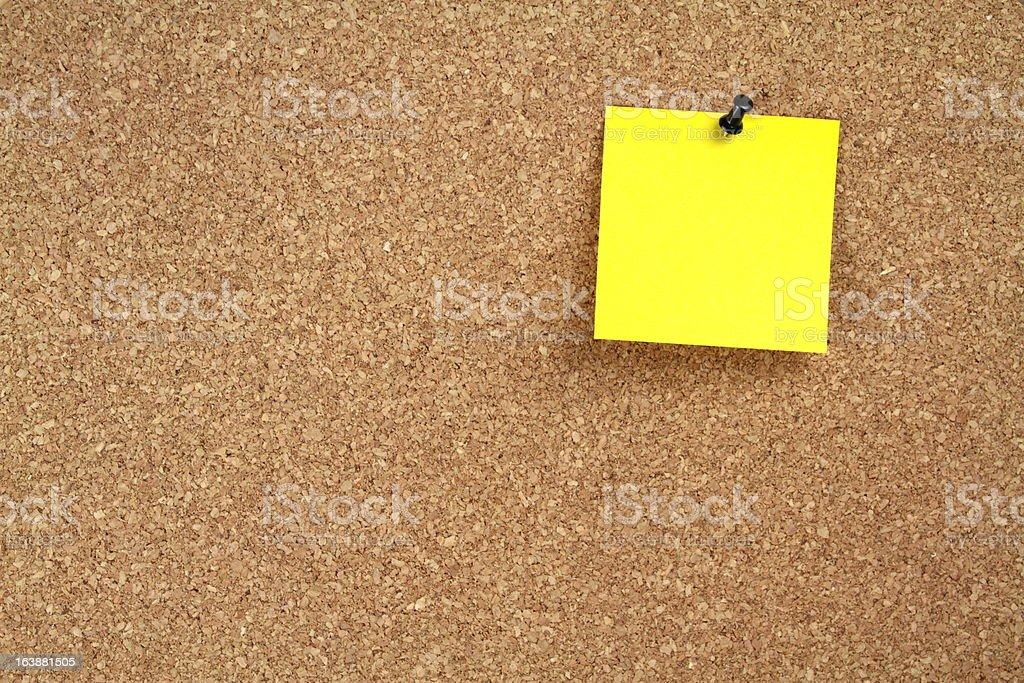 Yellow note paper on a cork board royalty-free stock photo