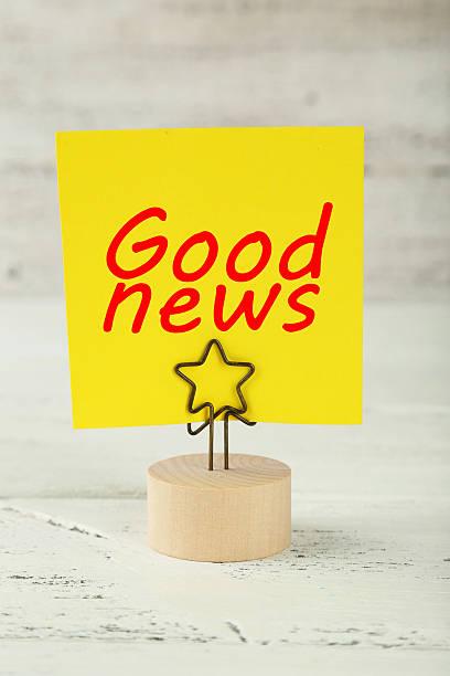 giallo nota su un titolare di carta su sfondo in legno bianco - buona notizia foto e immagini stock