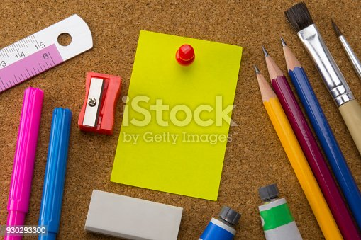 1062226450 istock photo yellow note paper pinned by red pushpin and school supplies on bulletin board 930293300