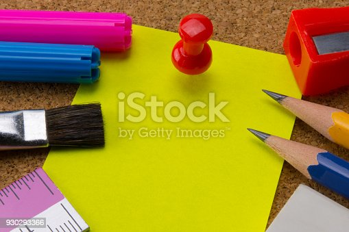 1062226450 istock photo yellow note paper pinned by red pushpin and school supplies on bulletin board 930293366