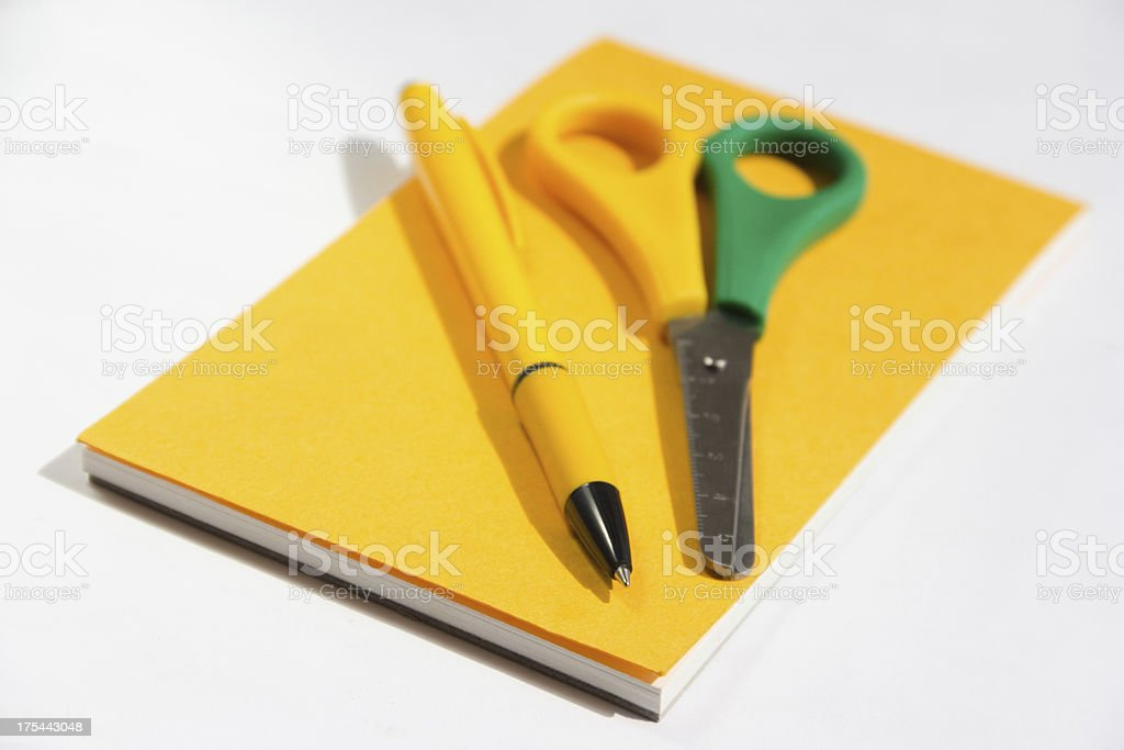 yellow notebook with a pen and scissors royalty-free stock photo