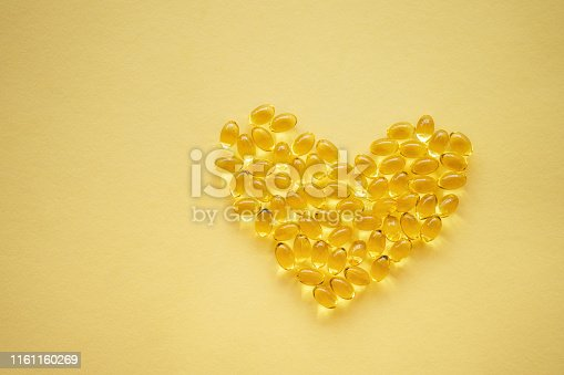 Yellow nutritional supplement pills on a yellow background