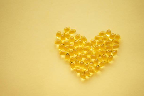 Gelbe Nahrungsergänzungsmittel Pillen in Herzform auf gelbem Hintergrund – Foto