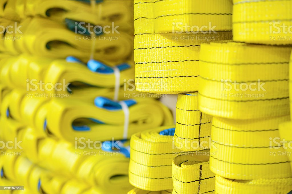 Yellow nylon soft lifting slings stacked in piles. stock photo