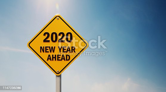 Yellow off road traffic sign with 2020 new year ahead text on blue sky. Horizontal composition with copy space.