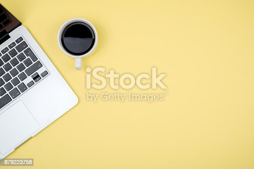 istock Yellow office desk table with computer. Top view with copy space 879223758
