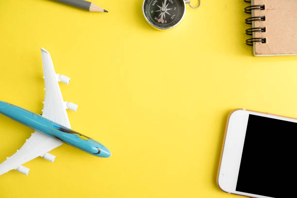 yellow office desk with smart phone and stationary supplies. top view with copy space, flat lay. - phone, travelling, copy space imagens e fotografias de stock