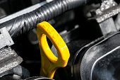 istock Yellow oil dipstick in car engine. Measuring level of engine oil. Dipstick oil level gauge with yellow color for Checking engine oil level of engine system. 1171368377
