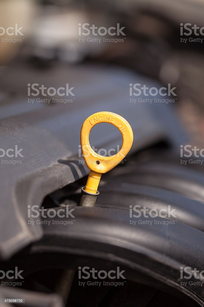 Yellow oil dipstick in the car stock photo