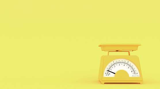 Yellow old kitchen weight scales on yellow background with free space for text or logo.