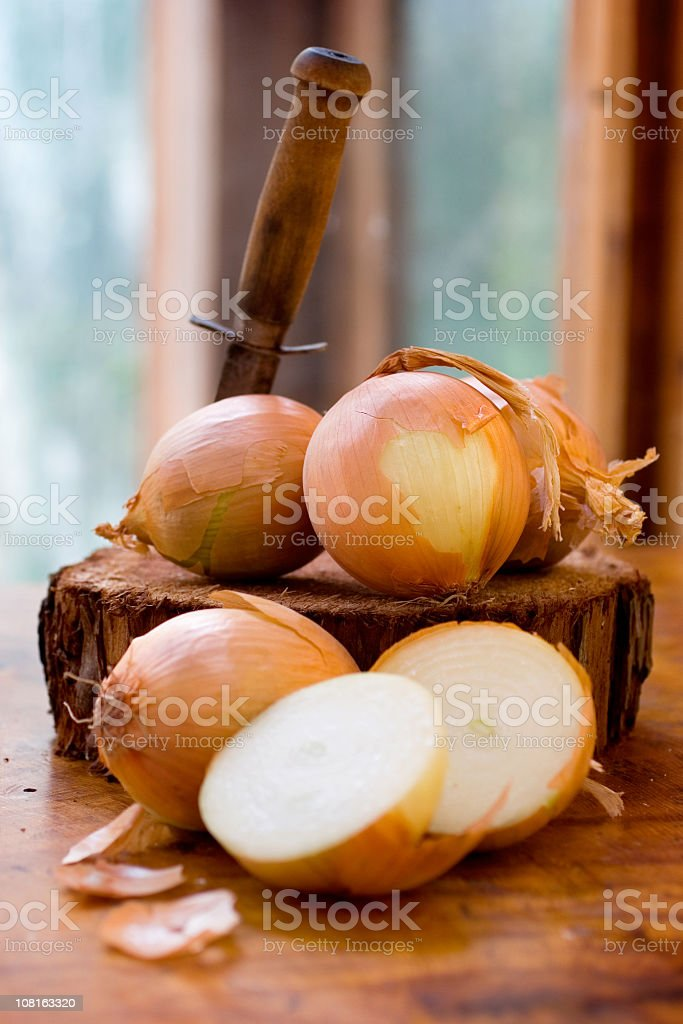 Yellow onions resting on wooden chopping block stock photo