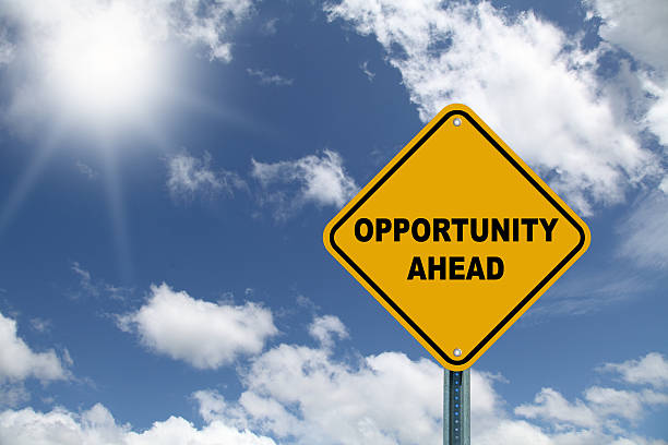 Yellow opportunity ahead road sign with sky stock photo