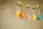 Copyspace of five Easter eggs hanging from a cord to exhibit them during holidays season.
