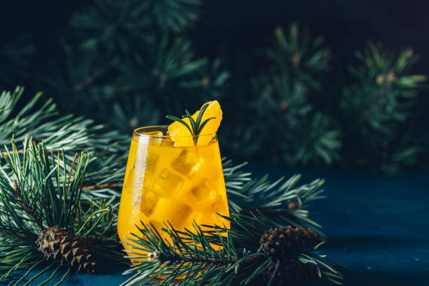 Yellow orange cocktail with tangerine and rosemary in glass on dark blue concrete background decorated pine branches with cones, close up. Christmas and New Year holiday welcome drink stock photo