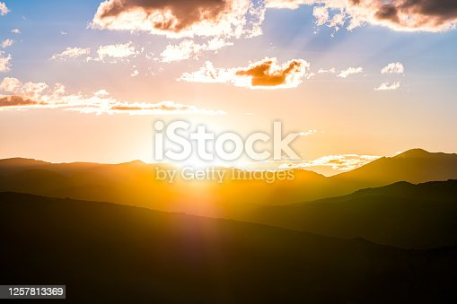 Yellow orange colorful sunset with sun rays flare in Aspen, Colorado USA with aerial view on Rocky Mountains Peak mountain ridge silhouette clouds at twilight
