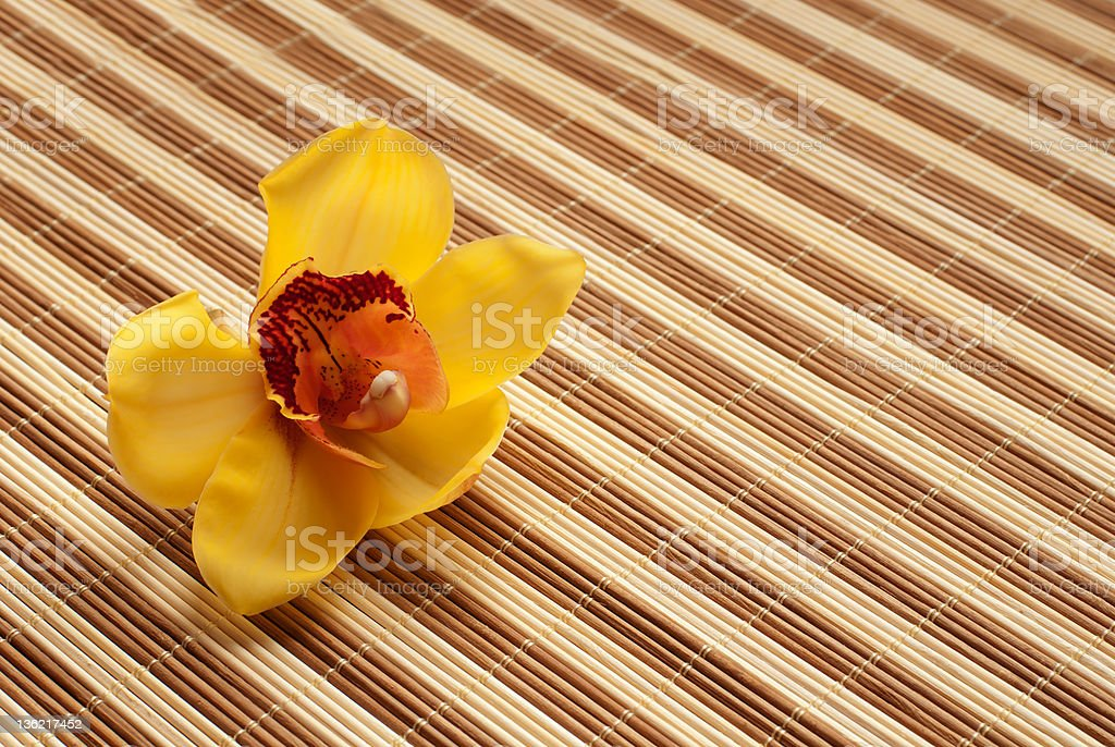 Yellow Orchid on bamboo napkin royalty-free stock photo