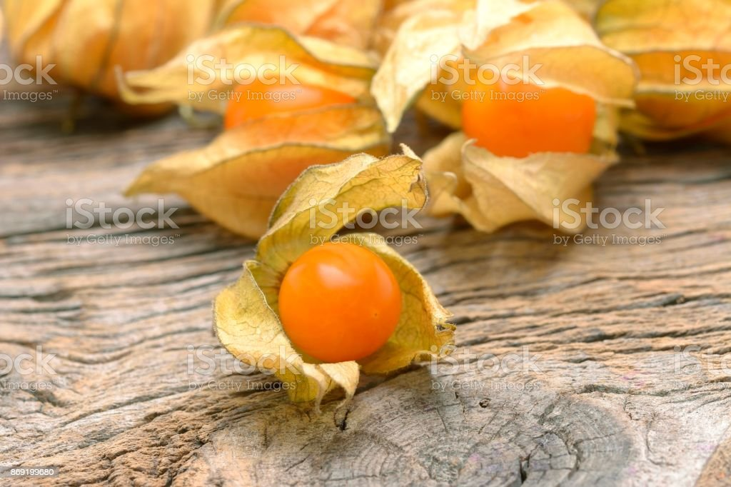 yellow organic physalis on a wooden board stock photo